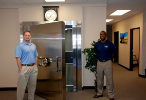 Kipp Bockhop, left, and former Denver Bronco Frank Robinson, two of the co-owners of Colorado Vault & Safe Deposit Box Co., display their huge vault at their Centennial business office